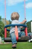Bébé garçon mignon observant de retour sur l'oscillation Image libre de droits