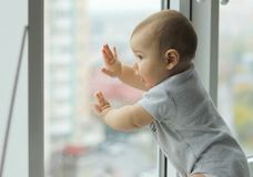 Bébé garçon mignon regardant à la fenêtre images libres de droits