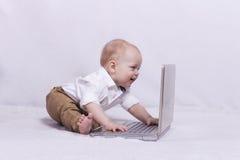Bébé garçon mignon regardant quelque chose l'ordinateur portable Images stock