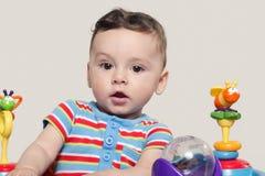 Bébé garçon mignon s'asseyant et jouant avec des jouets Photos stock