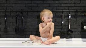 Bébé garçon mignon s'asseyant sur la table de cuisine touchant et goûtant le sucre et le mangeant Avoir l'amusement Avoir l'amuse clips vidéos