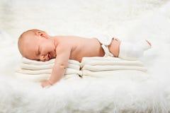 Bébé garçon mignon se trouvant sur la pile de serviettes Photo stock