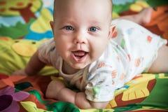 Bébé garçon mignon sur sa couverture gaie Photographie stock libre de droits