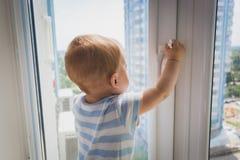 Bébé garçon mignon tirant par la poignée de fenêtre Concept d'enfant dedans Photos stock