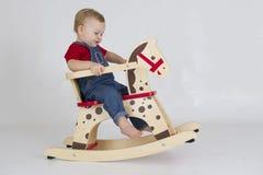 Bébé garçon montant un cheval de basculage en bois images libres de droits