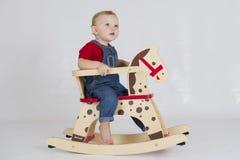 Bébé garçon montant un cheval de basculage en bois photo stock