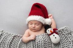 Bébé garçon nouveau-né avec le jouet de peluche de Santa Hat et de bonhomme de neige Image stock