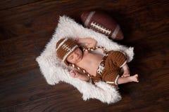 Bébé garçon nouveau-né dans l'équipement du football Image libre de droits