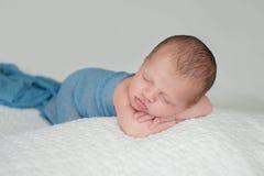 Bébé garçon nouveau-né de sommeil enveloppé dans le bleu Images stock