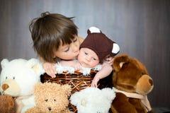 Bébé garçon nouveau-né mignon dans le panier avec le chapeau d'ours de nounours, regardant Photographie stock