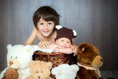 Bébé garçon nouveau-né mignon dans le panier avec le chapeau d'ours de nounours, regardant Photos stock