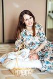 Bébé garçon nouveau-né se situant dans un panier, maman frottant un nouveau-né Photo stock