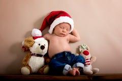 Bébé garçon nouveau-né utilisant un chapeau et des jeans de Noël, dormant dessus Photos libres de droits