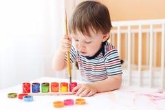 Bébé garçon peignant à la maison Photos libres de droits