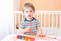 Bébé garçon peignant à la maison Image stock