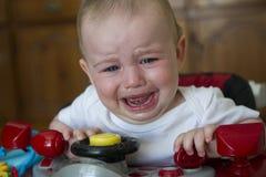 Bébé garçon pleurant dans un marcheur rouge de voiture de course photo stock