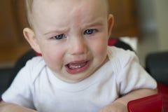 Bébé garçon pleurant dans un marcheur rouge de voiture de course photos stock