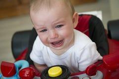 Bébé garçon pleurant dans un marcheur rouge de voiture de course images stock