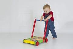 Bébé garçon poussant le chariot complètement des blocs en bois photographie stock