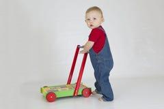 Bébé garçon poussant le chariot complètement des blocs en bois photos libres de droits