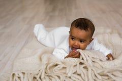 Bébé garçon riant de métis se trouvant sur le ventre à la maison Image stock