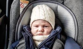 Bébé garçon sérieux dans le siège de voiture image libre de droits