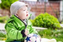Bébé garçon s'asseyant dans le temps de jardin au printemps photos stock