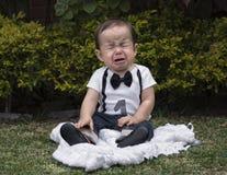 Bébé garçon s'asseyant dans pleurer de jardin Images libres de droits