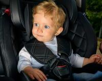 Bébé garçon s'asseyant dans un siège de voiture Images stock