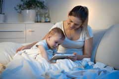 Bébé garçon s'asseyant sur le lit avec la mère et à l'aide du comprimé numérique à Photo libre de droits