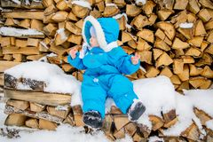 Bébé garçon s'asseyant sur une pile de bois de chauffage avec une neige d'hiver Photographie stock