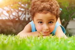 Bébé garçon se couchant sur le champ vert Photographie stock