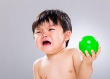 Bébé garçon se sentant peu satisfait de tenir son jouet photos libres de droits