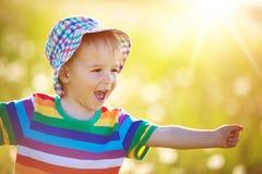 Bébé garçon se tenant dans l'herbe sur le fieald avec des pissenlits Images stock