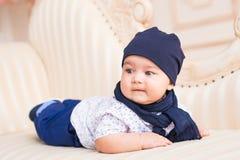 Bébé garçon se trouvant sur un sofa dans la chambre ensoleillée Photo libre de droits