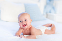Bébé garçon sur le lit blanc Photographie stock libre de droits