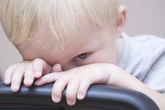Bébé garçon timide jetant un coup d'oeil au-dessus de la chaise Image libre de droits