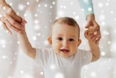 Bébé heureux apprenant à marcher avec l'aide de mère Photographie stock