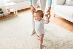 Bébé heureux apprenant à marcher avec l'aide de mère Images stock