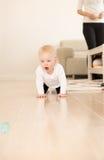 Bébé heureux avec des yeux bleus rampant au sol Image libre de droits