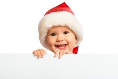 Bébé heureux dans un chapeau de Noël et un panneau d'affichage vide d'isolement dessus Photos stock