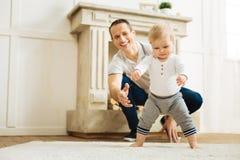 Bébé heureux essayant de se lever tandis qu'un père gai étant prêt à aider Photos stock