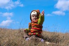 Bébé heureux s'asseyant sur un fond du ciel Photo stock
