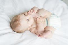 Bébé heureux mignon de 7 mois dans la couche-culotte se trouvant et jouant Photographie stock libre de droits