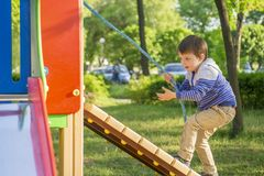 Bébé heureux mignon drôle jouant sur le terrain de jeu L'émotion du bonheur, amusement, joie Petit garçon actif jouant sur le ter photos libres de droits