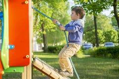 Bébé heureux mignon drôle jouant sur le terrain de jeu L'émotion du bonheur, amusement, joie Petit garçon actif jouant sur le ter images libres de droits
