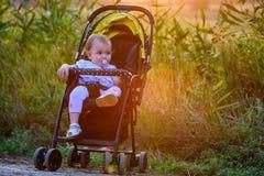 Bébé heureux s'asseyant dans la poussette moderne sur la promenade Photographie stock