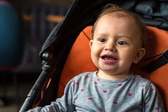 Bébé heureux s'asseyant dans la poussette moderne sur la promenade Images stock