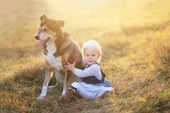 Bébé heureux s'asseyant dans le domaine avec le berger allemand adopté Pe Images libres de droits