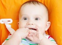 Bébé heureux s'asseyant sur la chaise de bébés Image stock